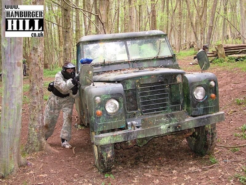 A Paintball player hiding behind a Land Rover